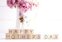 Un fondo di giorno di madri con la scrittura sui caratteri in grassetto con i fiori rosa in un vaso immagini stock libere da diritti