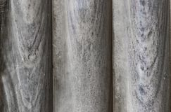 Un fondo di tre vecchie colonne di marmo ha confinato insieme su - il primo piano grigio con i toni blu fotografie stock