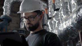 Un fontanero hace un control del sistema de la ventilación o de calefacción usando un artilugio almacen de metraje de vídeo