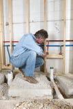 Fontanero que instala la agua corriente caliente y fría Fotografía de archivo libre de regalías
