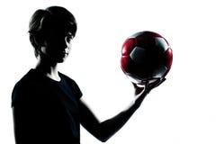 Un footba del fútbol de la explotación agrícola de la silueta del adolescente Imagen de archivo libre de regalías