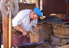 Un forgeron Dressed dans l'équipement traditionnel forge le métal d'un rouge ardent dans des épées Photo stock