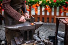 Un forgeron martelant un clou d'un rouge ardent de cheval à Noël tchèque de s photos stock