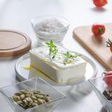 In un formaggio bianco del piatto con i verdi, i semi ed i pomodori di girasole sbucciati su un tavolo da cucina inutilizzato fotografie stock libere da diritti
