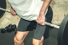 Un forte allenamento muscolare di sollevamento pesi del bilanciere dell'uomo nella palestra per forza ed i grandi muscoli Immagini Stock Libere da Diritti