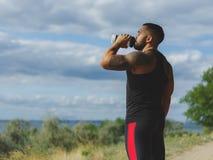 Un forte culturista con un corpo muscolare e un'acqua potabile del tatuaggio dopo un allenamento su un fondo vago naturale Immagini Stock