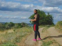 Un forte culturista con un corpo muscolare e un'acqua potabile del tatuaggio dopo un allenamento su un fondo vago naturale Immagini Stock Libere da Diritti