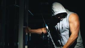 Un forte culturista fa gli esercizi del tricipite con una catena nella palestra stock footage