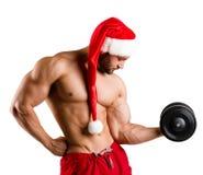 Un forte giovane uomo sessuale del nuovo anno con l'ente muscolare nel rosso ed il natale bianco Santa ricoprono Immagine Stock