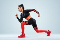 Un forte sprinter delle donne e atletico, eseguente uso nella motivazione degli abiti sportivi, di forma fisica e di sport Concet immagine stock libera da diritti