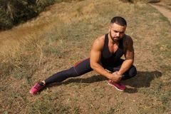 Un forte uomo muscolare con stoppia migliora la flessibilità allungando su uno sfondo naturale vago Immagine Stock Libera da Diritti