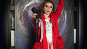 Un fotógrafo de la chica joven se está colocando con la cámara en sus manos, pensando en la determinación del marco Explica algo almacen de video