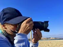 Un fotógrafo de la mujer toma una imagen en la playa imagen de archivo libre de regalías