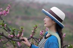 Un fotógrafo de sexo femenino en el jardín del melocotón con el sombrero Foto de archivo