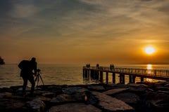 Un fotógrafo en la playa en la puesta del sol dibuja Foto de archivo libre de regalías