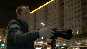 Un fotógrafo profesional, fotografías el movimiento de coches por la tarde almacen de video