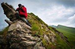 Un fotógrafo que se sienta en algunas rocas escarpadas Foto de archivo