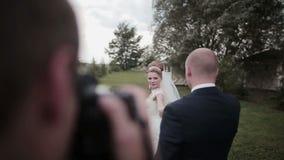 Un fotógrafo toma imágenes de un par joven hermoso en su día de boda metrajes