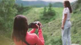 Un fotógrafo toma a un turista modelo en las montañas almacen de metraje de vídeo