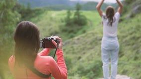 Un fotógrafo toma un vídeo de un alza de la montaña metrajes