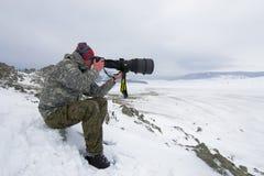 Un fotografo con la macchina fotografica che gode della natura nevosa Immagine Stock