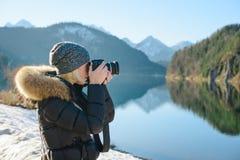 Un fotografo della donna sta prendendo l'immagine del lago e delle montagne Fotografia Stock