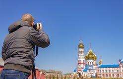 Un fotografo prende le immagini della chiesa sulla macchina fotografica con un treppiede fotografia stock