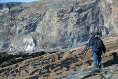 Un fotografo professionista su posizione che guarda la marea per ritirarsi sulla spiaggia rocciosa come considera dove installare Immagini Stock Libere da Diritti
