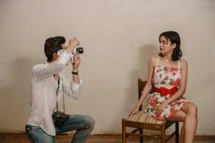 Un fotografo sta facendo una foto di un modello castana sveglio Immagine Stock