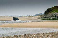 Un four-wheel-drive en agua entre las dunas de arena Fotografía de archivo libre de regalías