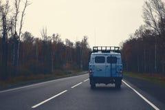 Un fourgon bleu conduisant sur une route le long de la forêt Photo stock