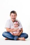 Un frère heureux plus âgé jugeant la soeur nouveau-née mignonne de bébé d'isolement sur le fond blanc Photo libre de droits