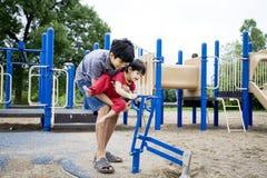 Un frère plus âgé aidant l'enfant de mêmes parents handicapé Images libres de droits