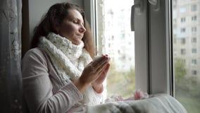 Un frío, estornudos enfriados de la mujer Muchacha que sopla su nariz mientras que se sienta en la ventana metrajes