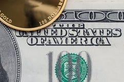 Un fragment de pièce d'or avec une valeur nominale de 100 dollars et billets d'un-cent-dollar photo libre de droits