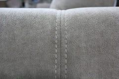 Un fragmento de la parte posterior de un sofá gris del terciopelo imagen de archivo