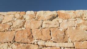 Un fragmento de una pared de piedra amarilla en un fondo del cielo azul metrajes