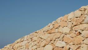 Un fragmento de una pared de piedra amarilla en un fondo del cielo azul almacen de video