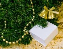 Un fragmento del árbol artificial, un regalo en una caja, decoros de la Navidad Fotos de archivo libres de regalías