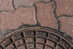 Un frammento del coperchio del pozzo e della pavimentazione sottragga la priorit? bassa Fuoco molle immagine stock