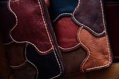 Un frammento di una borsa di cuoio e di una borsa fatte dei pezzi colorati multi Cucitura del cuoio bianco Fotografia Stock Libera da Diritti