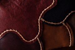 Un frammento di una borsa di cuoio e di una borsa fatte dei pezzi colorati multi Cucitura del cuoio bianco Fotografia Stock