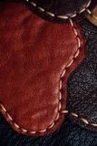 Un frammento di una borsa di cuoio e di una borsa fatte dei pezzi colorati multi Cucitura del cuoio bianco Immagini Stock Libere da Diritti