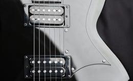 Un frammento di una chitarra nera con le corde d'acciaio Fotografia Stock