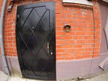 Un frammento di una facciata del mattone della casa con la porta Fotografia Stock Libera da Diritti