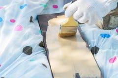 Un frammento di una mano gloved che dipinge un bordo di legno con un'ampia spazzola nel giallo fotografia stock