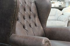 Un frammento di una sedia di cuoio classica Primo piano di struttura di cuoio elegante con i bottoni Frammento di una sedia class immagini stock libere da diritti