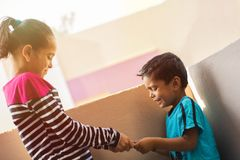 Un fratello di due bambini indiano e sorella o fratelli germani che combattono per il telefono cellulare ad all'aperto fotografie stock libere da diritti