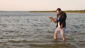 Un freelancer con un ordenador portátil en un traje de negocios y ningunos pantalones en el medio del mar disfruta entusiasta en almacen de video