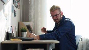 Un freelancer del hogar del loco con los vidrios y el pelo amarillo que trabajan en casa, usando un ordenador portátil Hombre tri metrajes
